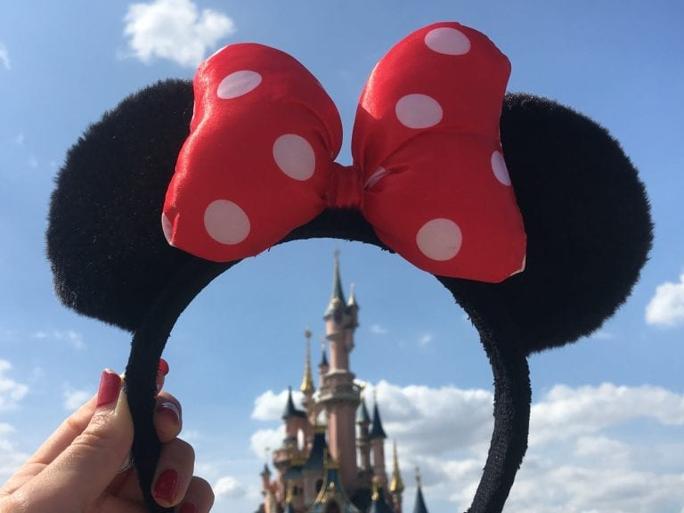person holding Minnie Mouse headband overlooking castle